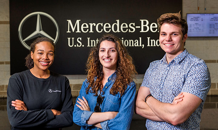 Students standing in front of Mercedes-Benz sign